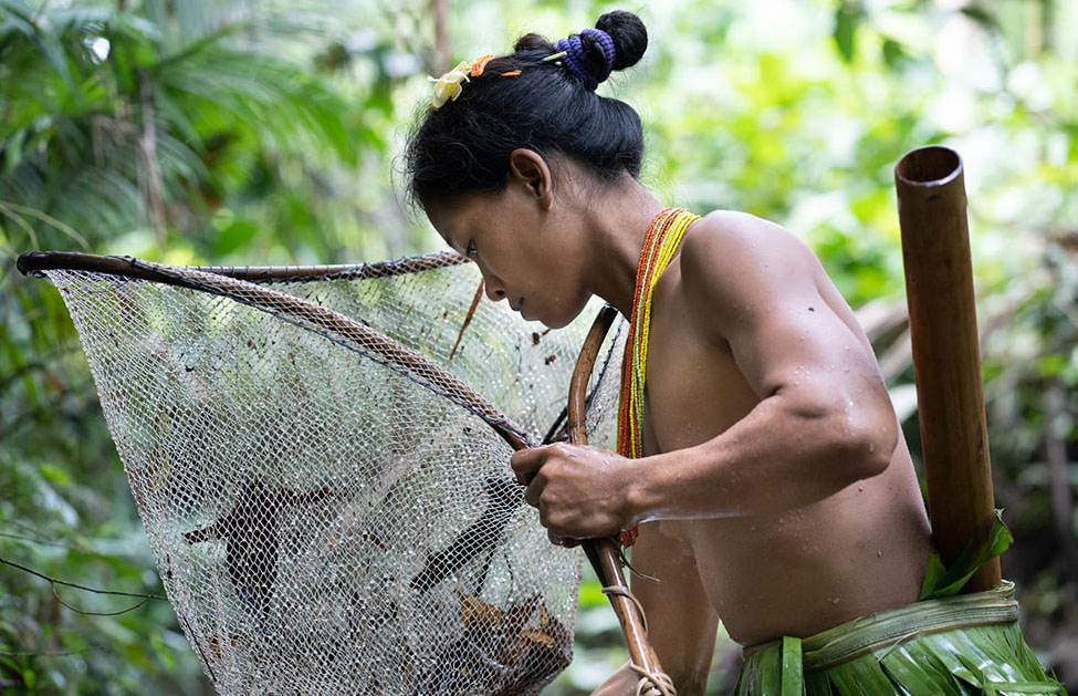 Bai Tiru, a Mentawai mother fishes in the river for crabs, shrimp, and fish.