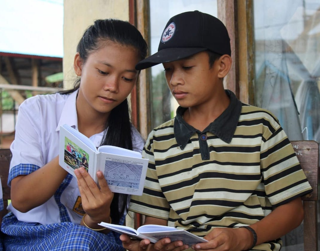 Indigenous Mentawai school student communicates with a young boy using the Mentawai language dictionary, published by @sukumentawai in 2019